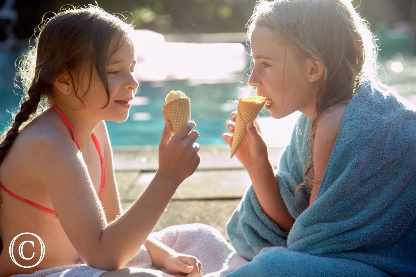 Girls eating ice creams by the side of the pool.