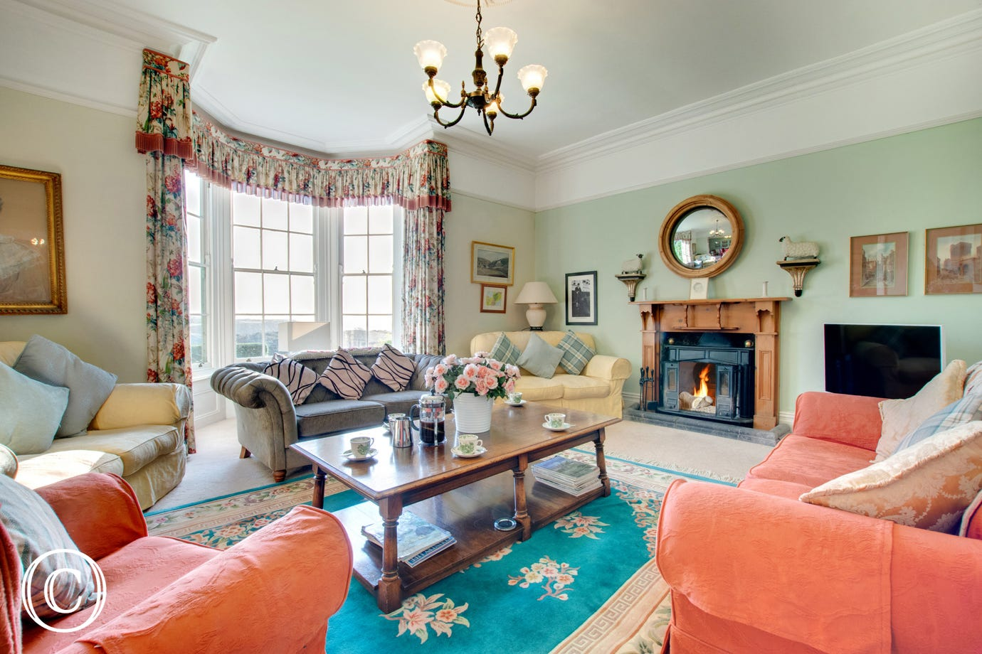 The large drawing room with bay window looking out over the lawns and sea views beyond.