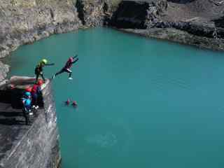 People jumping into water from a cliff